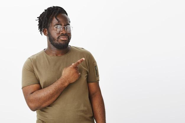 Portrait de gars incertain avec des lunettes posant contre le mur blanc