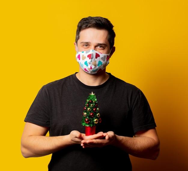Portrait de gars en masque avec arbre de noël