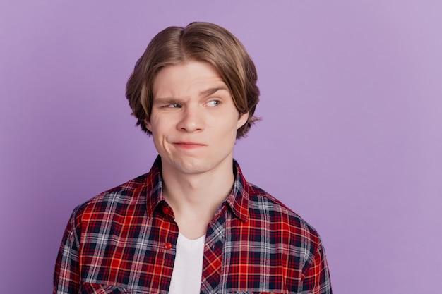 Portrait d'un gars méfiant et méfiant lever les sourcils côté espace vide sur fond violet