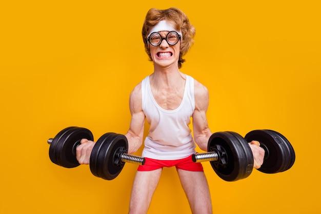 Portrait de gars motivé soulevant des haltères faisant de l'exercice