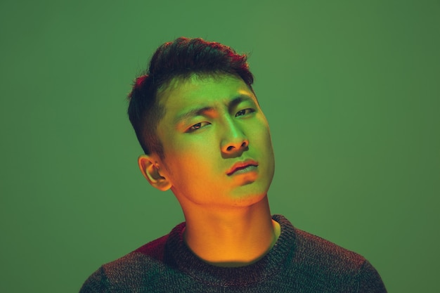 Portrait d'un gars avec néon coloré sur fond vert studio. modèle masculin d'humeur calme et sérieuse. expression faciale, cyberpunk, style de vie des milléniaux et apparence. avenir, technologies.