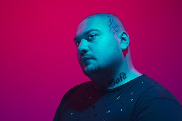 Portrait d'un gars avec néon coloré sur mur rouge. modèle masculin d'humeur calme et sérieuse. l'expression du visage, le style de vie des millénaires et l'apparence. avenir, technologies.