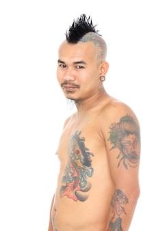Portrait d'un gars punk asiatique souriant avec une coiffure mohawk, un piercing et un tatouage isolé sur fond blanc