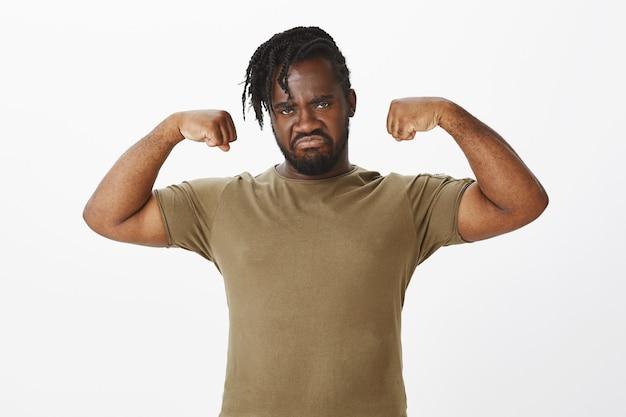 Portrait de gars sérieux dans un t-shirt marron posant contre le mur blanc