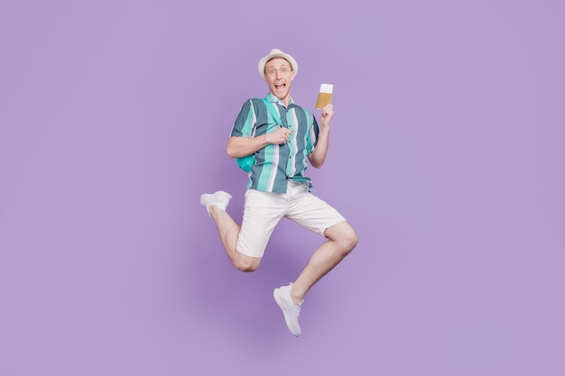 Portrait d'un gars touristique positif génial et étonné jump run hold billets passeport sur fond violet