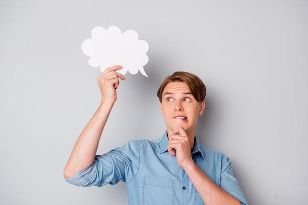 Portrait de gars troublé d'esprit tenir bulle papier blanc carte hésiter