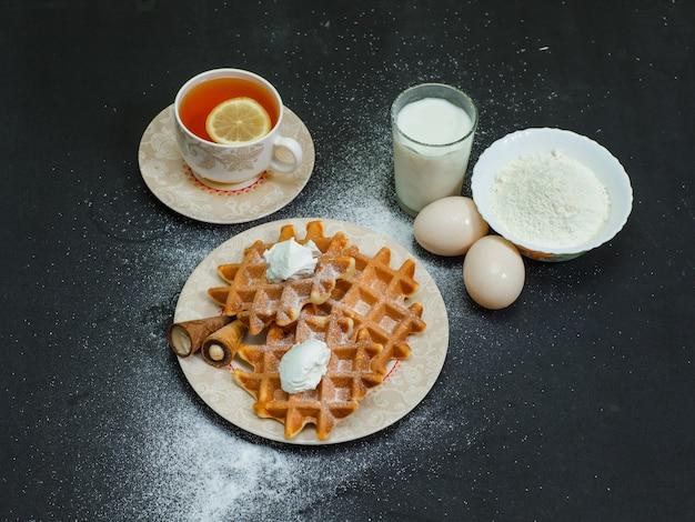 Portrait de gaufres en plaque avec du thé, des œufs, de la farine, du lait à l'obscurité. horizontal