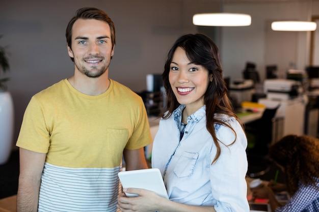 Portrait de gens d'affaires créatifs souriants debout au bureau