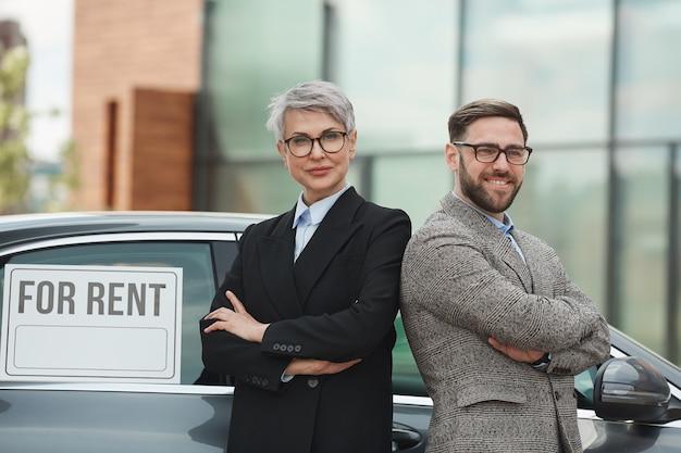 Portrait de gens d'affaires debout, les bras croisés et souriant contre la voiture de location