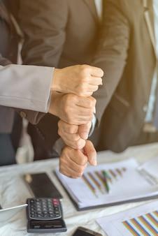 Portrait des gens d'affaires empilant la main ensemble en utilisant comme arrière-plan (concept de travail d'équipe et de partenariat