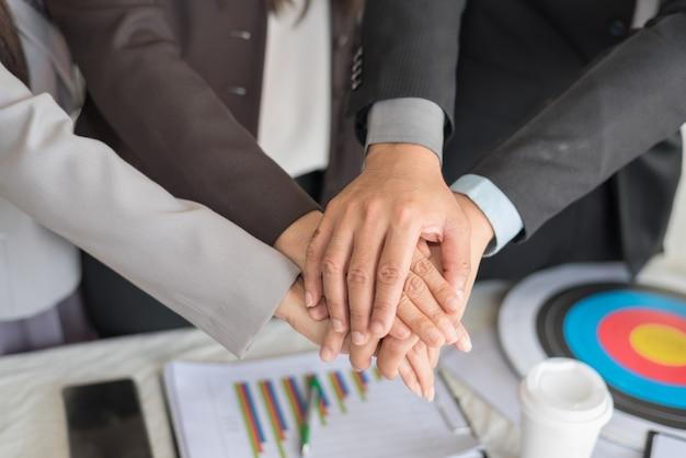 Portrait de gens d'affaires empilant la main ensemble en utilisant comme mur (concept de travail d'équipe et de partenariat)
