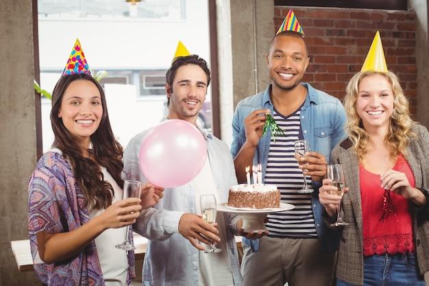 Portrait des gens d'affaires occasionnels célébrant l'anniversaire au bureau