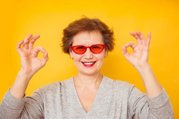 Portrait de geste de femme âgée ou montrant les mains ok sur fond jaune.