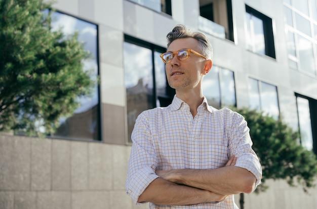 Portrait de gestionnaire d'âge moyen réussi debout à l'extérieur