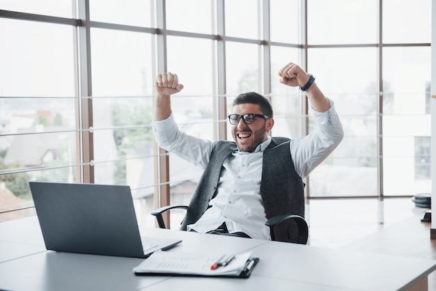 Portrait d'un gestionnaire de banquier drôle impressionné excité au bureau.