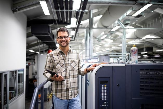 Portrait de gestionnaire d'impression debout près d'une grande machine d'impression offset dans une usine d'impression.