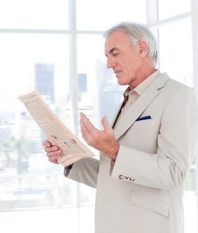 Portrait d'un gestionnaire mature lisant un journal