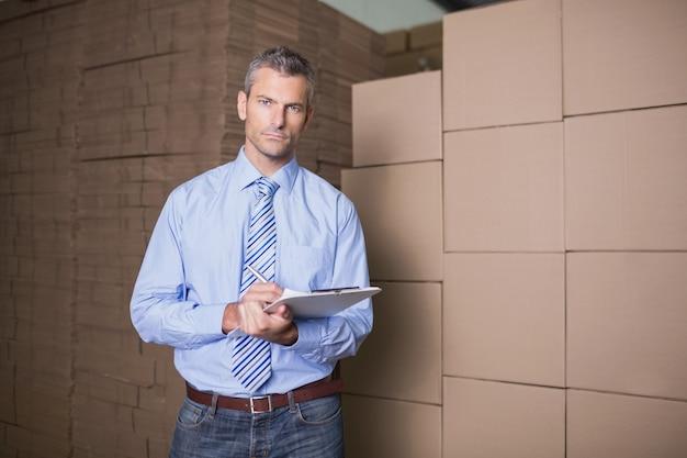 Portrait de gestionnaire avec le presse-papier dans l'entrepôt