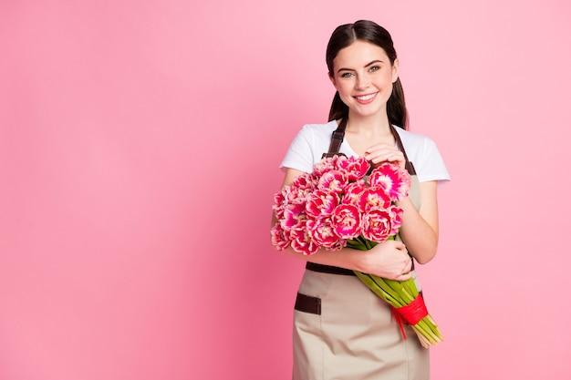 Portrait de gestionnaire de vente au détail de fille séduisante tenant des fleurs de printemps romantiques
