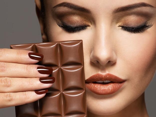 Portrait de glamour belle femme aux ongles bruns tient une barre de chocolat