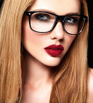 Portrait glamour sensuel du beau modèle de femme blonde avec un maquillage quotidien frais avec des lèvres violettes et une peau propre et saine dans des verres