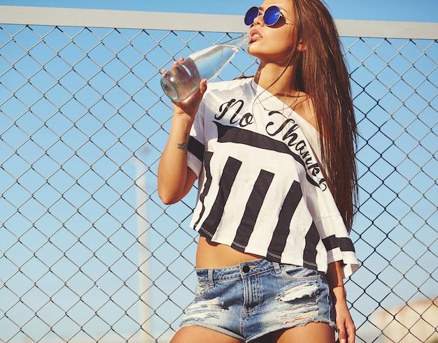 Portrait de glamour sexy élégant belle jeune femme modèle dans des vêtements décontractés d'été hipster lumineux posant dans la rue derrière une grille de fer et un ciel bleu. boire de l'eau en bouteille
