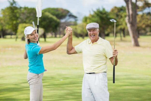 Portrait, golfeur, couple, donner, élevé, cinq