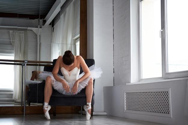 Portrait de gracieuse ballerine assise et posant sur un fauteuil à l'école de ballet. copyspace