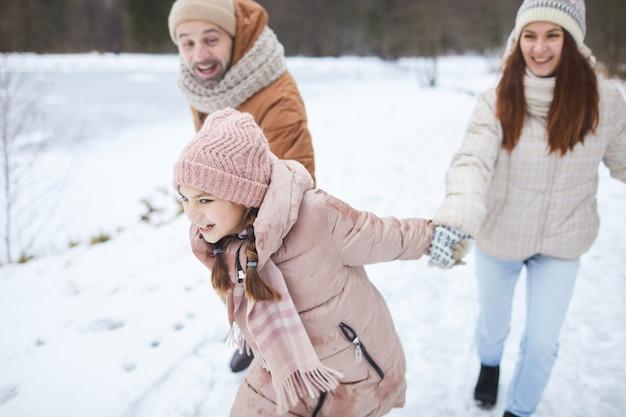 Portrait en grand angle d'une adolescente enjouée tenant la main de ses parents et les tirant tout en profitant d'une promenade en famille dans la forêt d'hiver