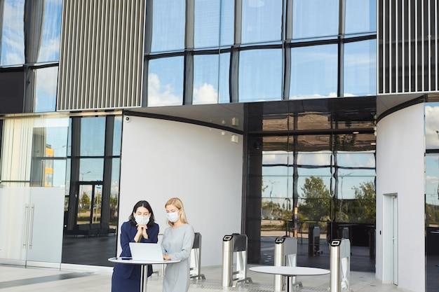 Portrait grand angle de deux femmes d'affaires réussies portant des masques tout en regardant l'écran d'ordinateur portable debout au bureau dans un immeuble de bureaux,