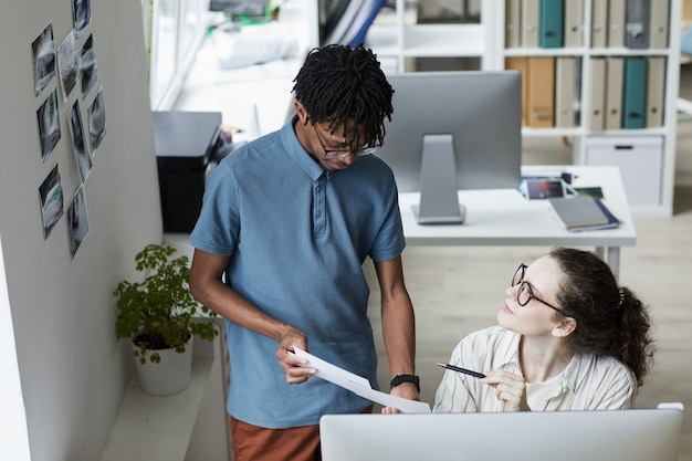 Portrait en grand angle de deux jeunes créatifs examinant des images tout en travaillant sur l'édition et la publication dans un bureau moderne, espace copie