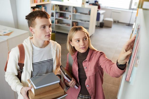 Portrait de grand angle de deux jeunes homme et femme prenant des livres sur étagère dans la bibliothèque de l'école,