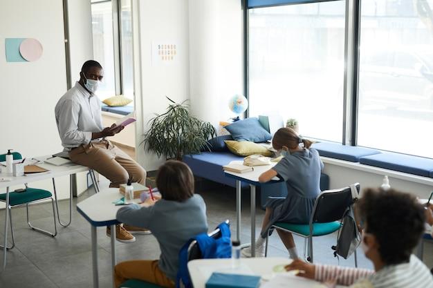 Portrait grand angle d'un enseignant afro-américain portant un masque dans une salle de classe, mesures de sécurité covid, espace de copie