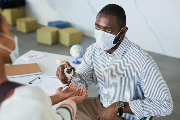 Portrait en grand angle d'un enseignant aidant les enfants à se désinfecter les mains lorsqu'ils entrent en classe à l'école, mesures de sécurité covid