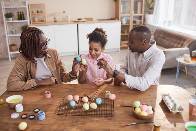 Portrait en grand angle d'une famille afro-américaine heureuse peignant des œufs de pâques ensemble tout en étant assis à une table en bois dans un intérieur confortable, décorations de pâques bricolage