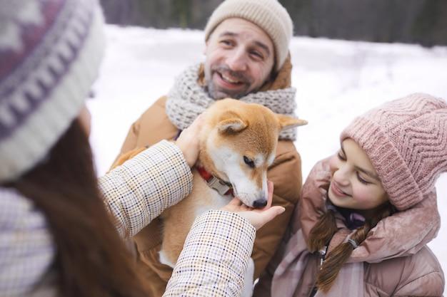 Portrait en grand angle d'une famille heureuse moderne jouant avec un chien de compagnie tout en profitant d'une promenade en plein air ensemble dans la forêt d'hiver
