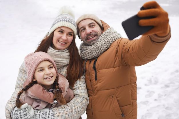 Portrait en grand angle d'une famille heureuse prenant une photo de selfie tout en profitant d'une promenade en plein air ensemble dans la forêt d'hiver