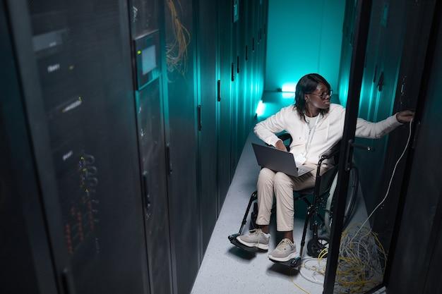 Portrait en grand angle d'une femme afro-américaine handicapée utilisant un ordinateur portable tout en travaillant dans la salle des serveurs, opportunité d'emploi accessible
