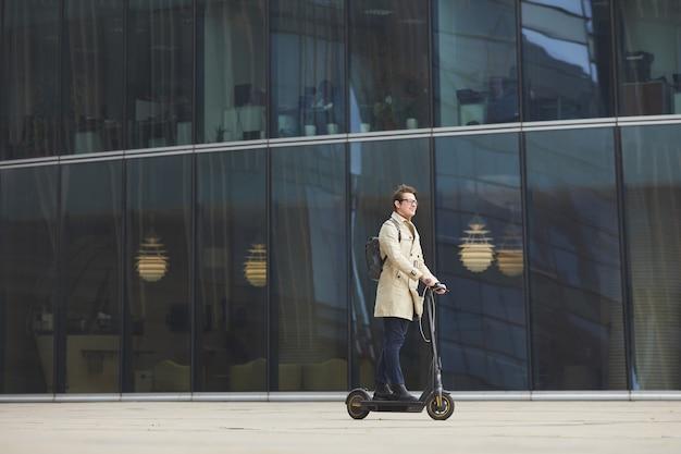 Portrait grand angle graphique de jeune homme d'affaires moderne équitation scooter électrique à travers tourné tout en se rendant au travail au centre-ville avec des bâtiments de la ville urbaine en arrière-plan, copiez l'espace