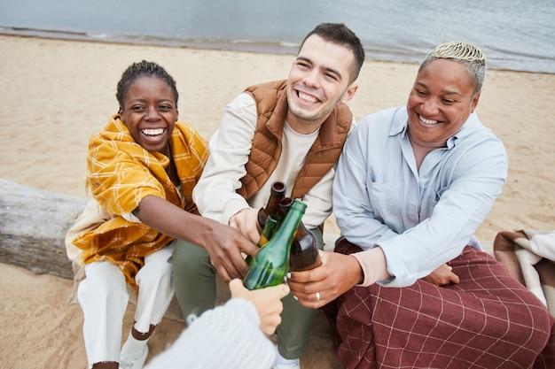 Portrait en grand angle d'un groupe diversifié d'amis buvant de la bière sur la plage en automne et riant joyeusement, espace de copie