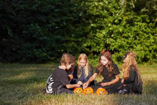 Portrait grand angle d'un groupe multiethnique d'enfants mangeant des bonbons à l'halloween à l'extérieur tout en portant des costumes, copiez l'espace