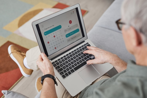 Portrait en grand angle d'un homme senior moderne utilisant un ordinateur portable tout en travaillant à domicile et en planifiant l'horaire, espace de copie
