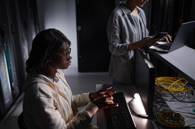 Portrait en grand angle d'une ingénieure réseau afro-américaine utilisant un ordinateur portable tout en travaillant dans une salle de serveur sombre, espace de copie