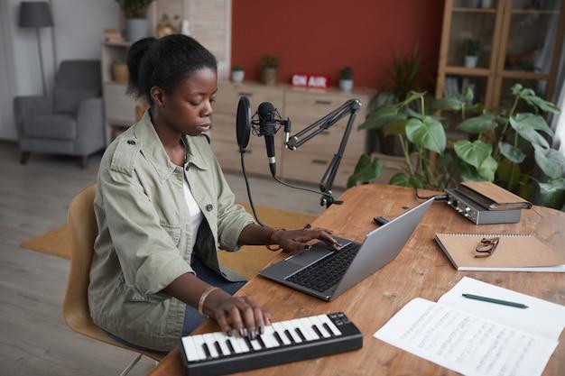 Portrait de grand angle de jeune femme afro-américaine composant de la musique en studio d'enregistrement à domicile, espace copie