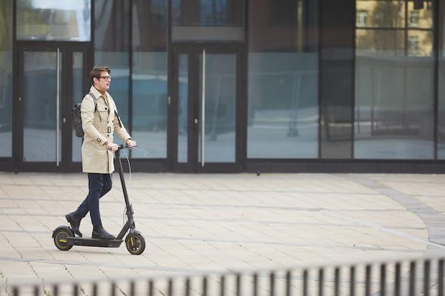 Portrait grand angle de jeune homme d'affaires moderne équitation scooter électrique tout en se rendant au travail avec les bâtiments de la ville urbaine en arrière-plan, copiez l'espace