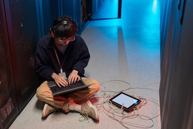 Portrait en grand angle d'un jeune homme asiatique utilisant un ordinateur portable assis sur le sol dans la salle des serveurs éclairée par la lumière bleue et mettant en place un réseau de superordinateurs, espace de copie