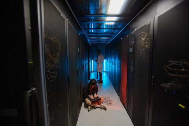 Portrait grand angle d'un jeune homme asiatique utilisant un ordinateur portable assis sur le sol dans la salle des serveurs éclairée par la lumière bleue et mettant en place un réseau de superordinateurs, espace de copie
