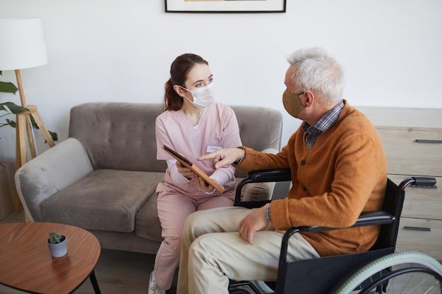 Portrait en grand angle d'une jeune infirmière aidant un homme âgé en fauteuil roulant à l'aide d'une tablette numérique à la maison de retraite, tous deux portant des masques, espace pour copie