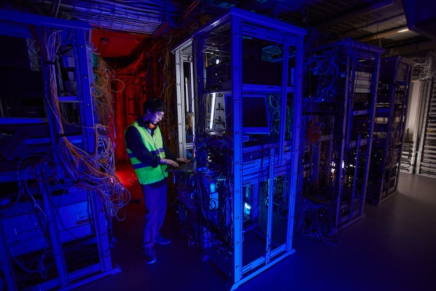 Portrait grand angle d'un jeune technicien réseau utilisant un ordinateur portable dans la salle des serveurs lors de la configuration de la connexion internet, espace de copie