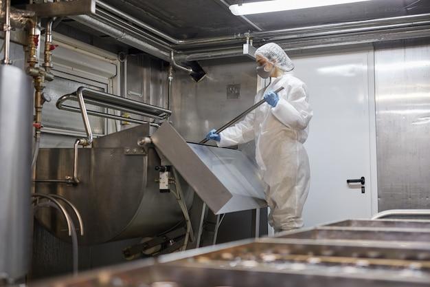 Portrait grand angle d'une jeune travailleuse mélangeant des produits dans une usine de fromages et de produits laitiers, espace pour copie